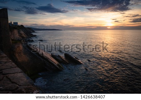 scenic view with sunset on atlantic ocean with rocks in socoa, basque country, france Royalty-Free Stock Photo #1426638407
