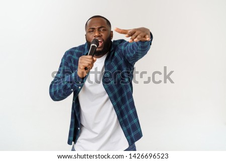 Portrait of cheerful positive chic handsome african man holding microphone singing song. Isolated on white background. #1426696523