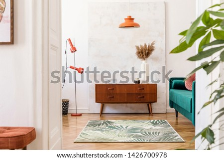 Stylish compositon of retro home interior with vintage cupboard, velvet sofa, flowers in vase, design orange lamps , elegant accessories and abstract paintings. Minimalistic concept. Nice home decor.  #1426700978