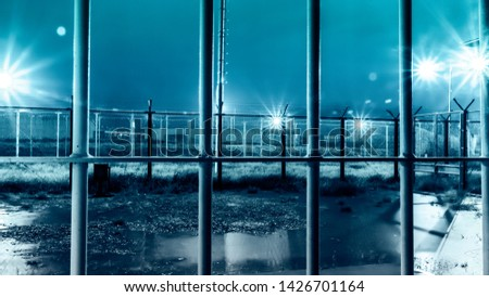 Dramatic Shot Of High Security Prison Facility Yard From Inside Iron Bars During Rain Storm At Night #1426701164