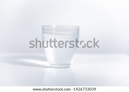 Round glass filled with cold mineral water on bright, blank surface. Reflection of the glass visible on the surface. High exposure photo. #1426733039