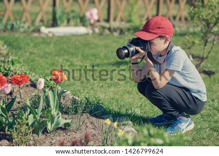 Cute European boy in a red baseball cap is taking picture of flowers in a beautiful garden.