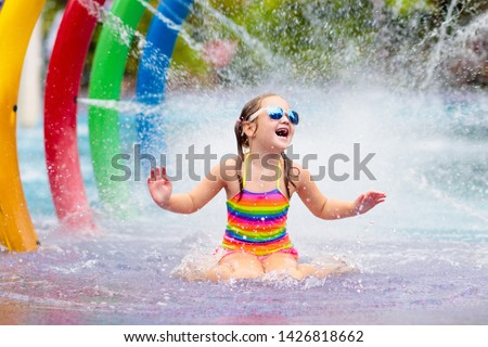 Kids play in aqua park. Children at water playground of tropical amusement park. Little girl at swimming pool. Child playing at water slide on summer vacation in Asia. Swim wear for young kid. #1426818662