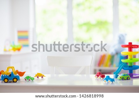 Little boy room. Desk with colorful toy cars. Nursery for young kid with educational vehicle and transport toys. Plastic car at rainbow parking garage. Home or kindergarten interior.  #1426818998