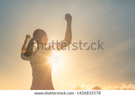 Strong woman, Winning, success , and life goals concept. Young woman with arms flexed facing the sunset.  #1426833578