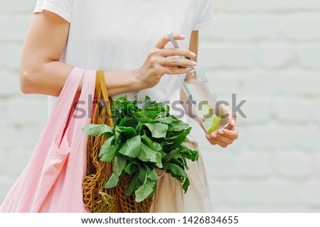 Female hands hold eco bag of vegetables, greens and reusable water bottle. Zero waste. Sustainable lifestyle concept. #1426834655