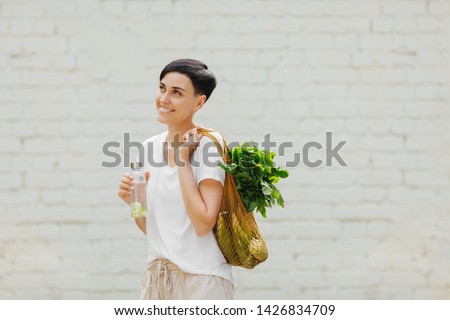 Young woman in light summer clothes with a eco bag of vegetables, greens and reusable water bottle.  Sustainable lifestyle. Eco friendly concept. Royalty-Free Stock Photo #1426834709