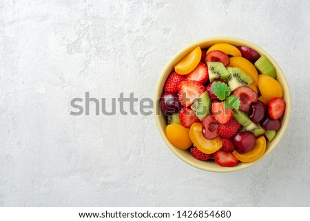 Healthy fresh fruit salad in bowl on gray concrete background. Top view. Copy space. #1426854680