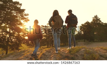 three girls travel, walk through woods to climb hill rejoice and raise their hands to the top. Hiker Girl. girls travel with backpacks on a country road. Happy family on vacation travels. #1426867163