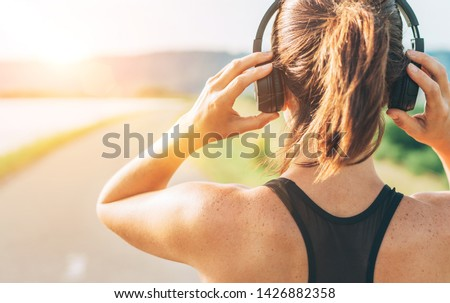 Close up image of teenager adjusting  wireless headphones before starting jogging and listening to music #1426882358