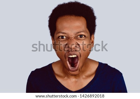 Portrait of Afro American man screaming at camera on studio. #1426892018