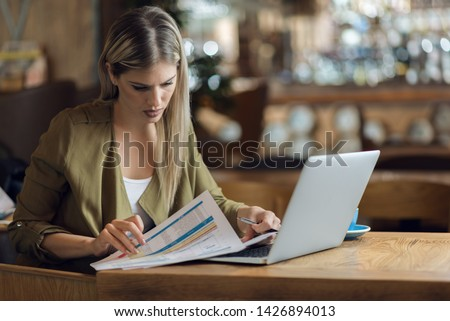 Businesswoman reading documents while working in a cafe #1426894013