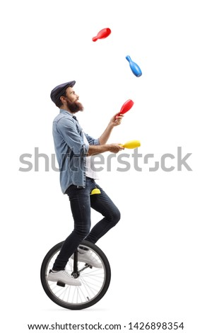 Full length profile shot of a male juggler on a unicycle juggling with clubs isolated on white background #1426898354