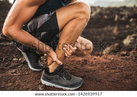 Achilles injury on running outdoors. Man holding Achilles tendon by hands close-up and suffering with pain. Sprain ligament or Achilles tendonitis. #1426929917