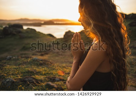 Woman praying alone at sunrise. Nature background. Spiritual and emotional concept. Sensitivity to nature #1426929929