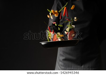 Chef cook fry fish with vegetables on a griddle on a black background. horizontal photo. sea food. healthy food. oriental cuisine, baner #1426945346