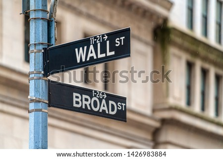 """Wall Street """"WALL ST"""" sign and broadway street over  NYSE stock market exchange building background. The New York Stock Exchange locate in economy district, Business and sing of landmark concept #1426983884"""