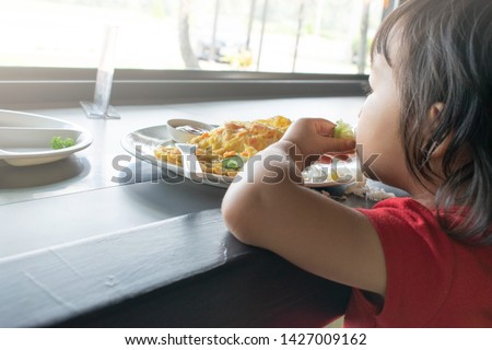 A child is trying to eat  by herself. Baby eating. #1427009162