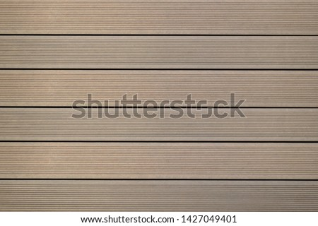 Top view of WPC in oak color. WPC: Wood-Plastic Composites are wood fiber and thermoplastic such as PE, PP, PVC, or PLA. A WPC decking are stylish and enrich the outdoor living #1427049401