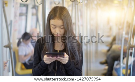 Beautiful Asia woman traveling and using the technology mobile phone in the Skytrain rails or subway for travel #1427075954