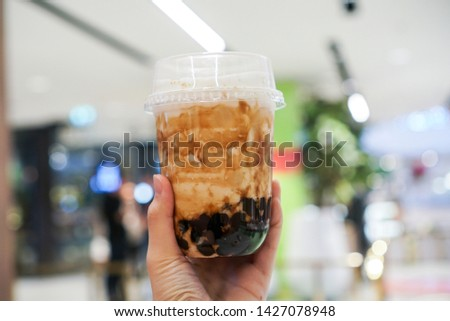 Brown sugar bubble drink. Woman holding a plastic cup of fresh milk and brown sugar boba/bubble toppings. Center focus. #1427078948