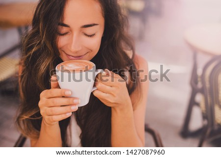 Young beautiful happy woman with long curly hair enjoying cappuccino in a street cafe #1427087960