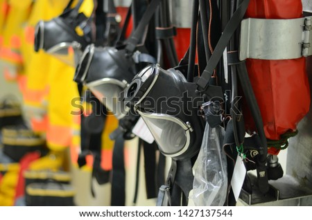 Full face mask with self contained breathing apparatus (SCBA) including fire suit and personal protective equipment (PPE) on the wall to stand by for firefighters at chemical plants, power plants. Royalty-Free Stock Photo #1427137544