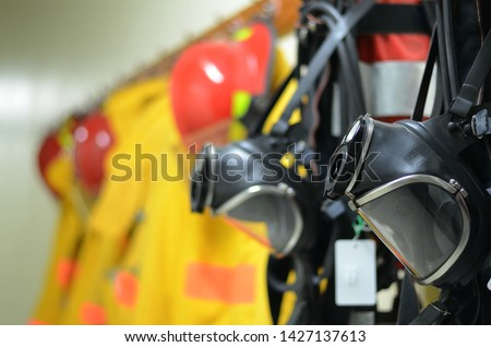 Full face mask with self contained breathing apparatus (SCBA) including fire suit and personal protective equipment (PPE) on the wall to stand by for firefighters at chemical plants, power plants. Royalty-Free Stock Photo #1427137613