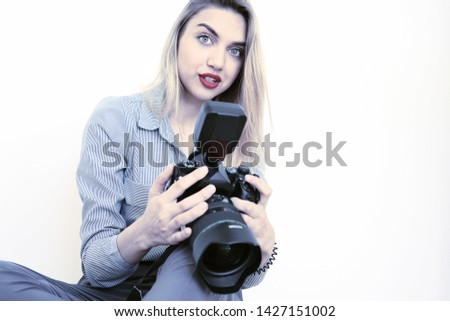 Beautiful young blonde with a big camera looks into the camera #1427151002