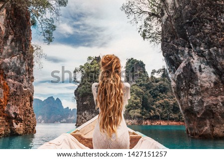 fashionable young model in boho style dress on boat at the lake  #1427151257