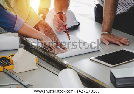 construction worker team planning about building plan with blueprint, safety helmet, construction tools on conference table at construction site, contractor, business, industry, construction concept #1427170187