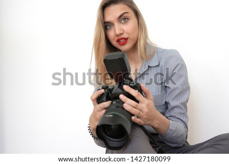 Beautiful young blonde with a big camera looks into the camera #1427180099