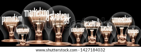 Photo of light bulbs with shining fibers in shapes of Marketing Strategy concept related words isolated on black background #1427184032
