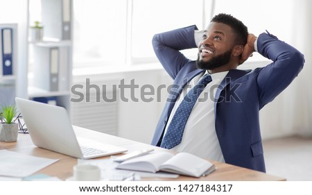 Break in work. Young african businessman in formalwear relaxing at workplace, free space #1427184317