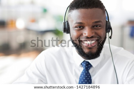 Operator of hot line. Portrait of cheerful african customer service representative with headset in call center, empty space Royalty-Free Stock Photo #1427184896