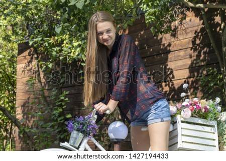Photo of Ukrainian long-haired Russian young model sitting on a bicycle decorated with flowers in the park in the summer on a sunny hot day #1427194433