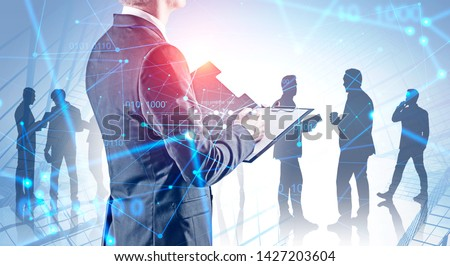 Rear view of businessman with clipboard and silhouettes of his team members over skyscraper background with double exposure of network interface. Concept of hi tech. Toned image #1427203604