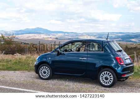 Tuscany, Italy - October 12, 2017: new version of the Fiat 500 parked on background rural field of Tuscany #1427223140