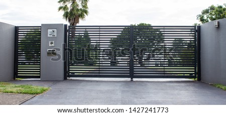 Metal driveway property entrance gates set in concrete fence with garden trees  in background Royalty-Free Stock Photo #1427241773