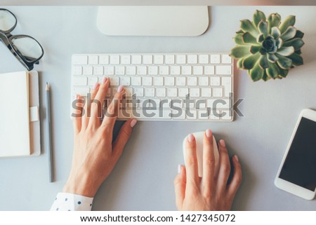 Top view of the workplace, elegant female hands on the keyboard of a personal computer in the office or at home, suitable for both freelancing and office content. Business lady prints  blog post  #1427345072