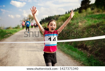 Small girl runner crossing finish line in a race competition in nature. #1427371340