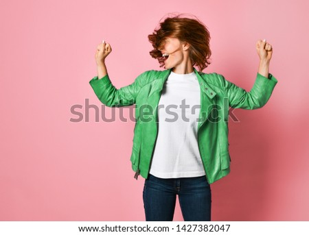 young woman wearing jeans and a jacket is shaking her head with her hair. The concept of joy, happiness, joy, fun #1427382047