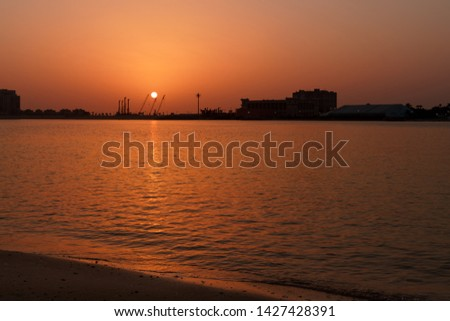 sunset in Pointe Beach Dubai. Sun is hiding behind cranes in the industrial urban background. Negative space created by the sea #1427428391