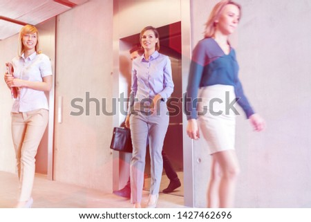 Business professionals walking out of elevator in office #1427462696