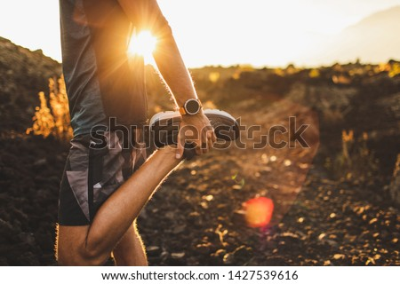 Male runner stretching leg and feet and preparing for running outdoors. Smartwatches or fitness tracker on hand. Beautiful sun light on background. Active and healthy lifestyle concept. #1427539616