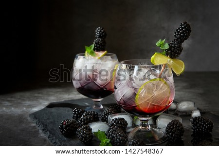 Seasonal soft drinks.Thirst in hot summer time. Two glasses of ice ,water ,lime and mulberry berries with mint on a dark background .Keto diet,soft drinks and alcoholic beverages. #1427548367