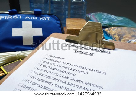 Disaster preparedness checklist on a clipboard with disaster relief items in the background.Such items would include a first aid kit,flashlight,tinned food,water,batteries and shelter. #1427564933