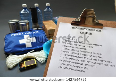 Disaster preparedness checklist on a clipboard with disaster relief items in the background.Such items would include a first aid kit,flashlight,tinned food,water,batteries and shelter. #1427564936