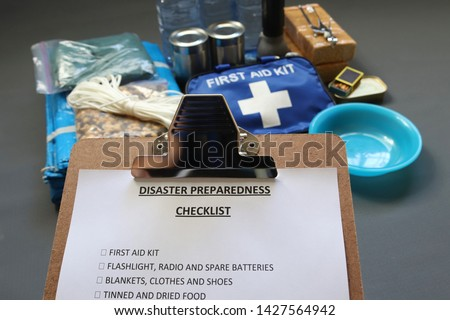 Disaster preparedness checklist on a clipboard with disaster relief items in the background.Such items would include a first aid kit,flashlight,tinned food,water,batteries and shelter. #1427564942