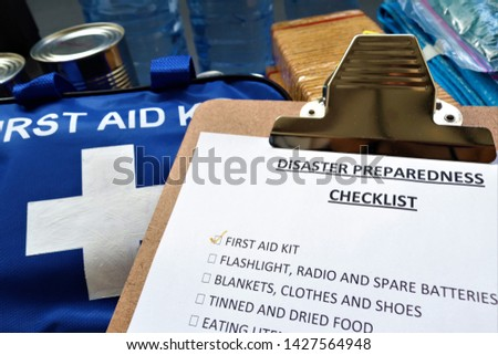 Disaster preparedness checklist on a clipboard with disaster relief items in the background.Such items would include a first aid kit,flashlight,tinned food,water,batteries and shelter.Be prepared. #1427564948